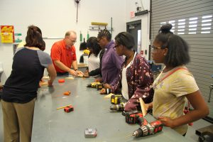 Bill Harmon and Holly Bauman working with Career Launch teens on wood peg game project
