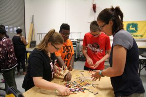 Holly Bauman working with Career Launch teens on wood peg game project