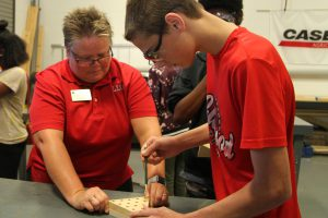 Dr. Lesley Frederick assisting Career Launch teens with wood peg game project