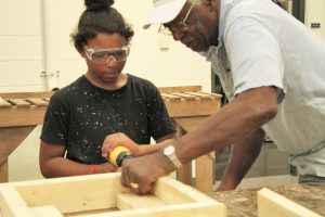 Jim Betts assisting Career Launch teen in constructing a washer toss game box