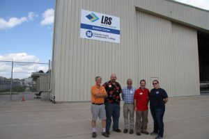 Dave Pietrzak, Arnold Tullis, Todd Cole, Rick Stillman and Christina Courier in front of new sign at aviation center
