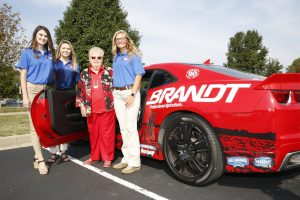 Evelyn Brandt Thomas with LLCC ag students in front of Brandt car
