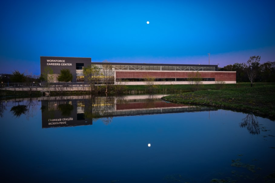 Workforce Careers Center at dusk. Pond in foreground, building and moon above.