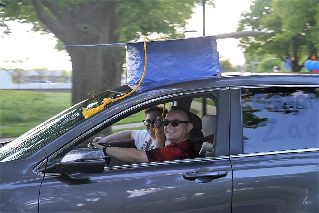 large grad cap on top of car in parade