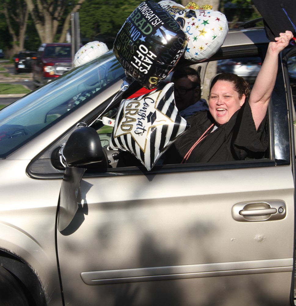 Excited grad in van at parade