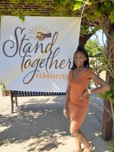 Kylana Moore next to Stand Together Scholarship sign