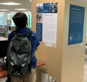 Student looking at 9/11 poster on library pillar