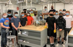 Students in the sheet metal fabrication class pose for a photo with the scorpion they created out of ductwork.