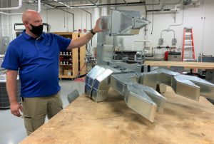 LLCC HVAC instructor Derek Matlock gestures toward the ductwork scorpion while explaining how it was assembled.